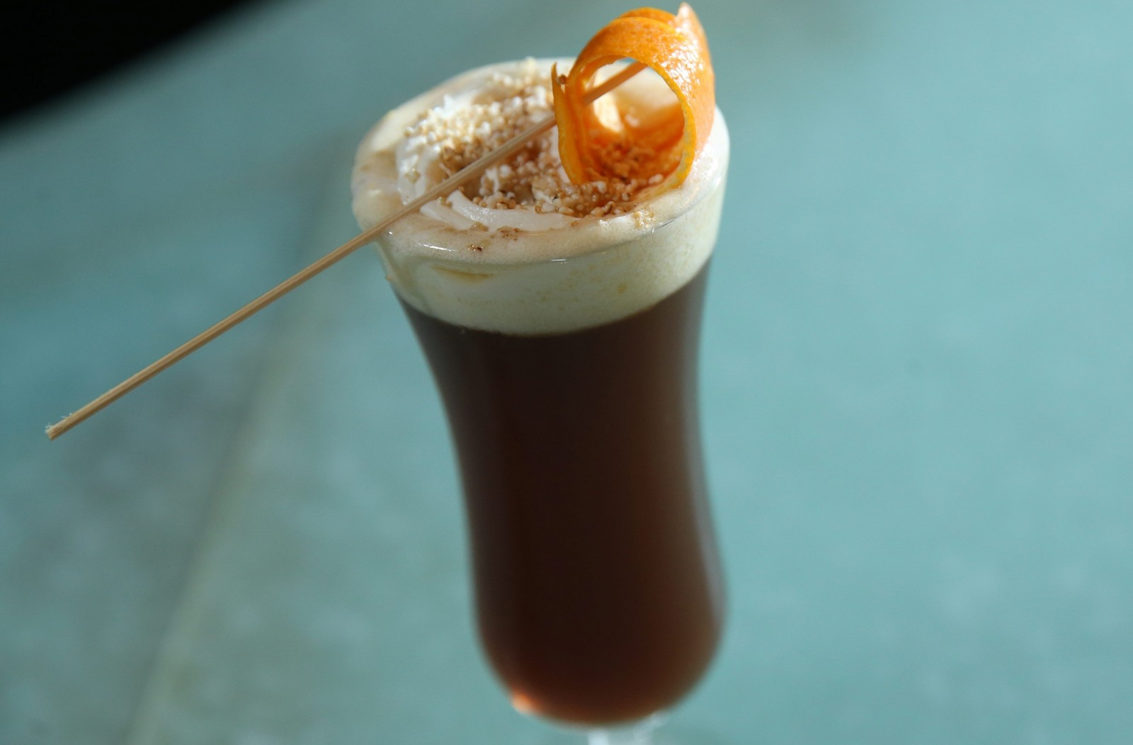 Bourbon & Butter's new winter drink called the Female Dog, made with rye whiskey infused with preserved plum, amaranthe and sesame, Public Revolution Coffee, sesame and topped with butter cream and amaranth garnished with orange peel. (Sharon Cantillon/Buffalo News)